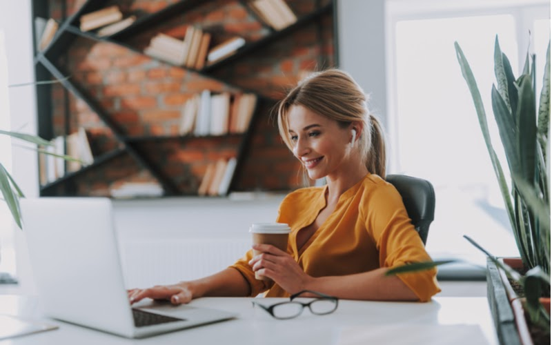 Woman drinking coffee and using a laptop