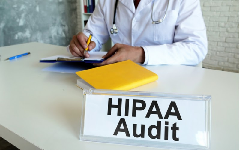 A doctor sitting at a table with a HIPAA audit sign
