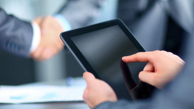 Image of a handshake and signing tablet. Use electronic signatures in Mexico to complete contracts and agreements easily and legally.