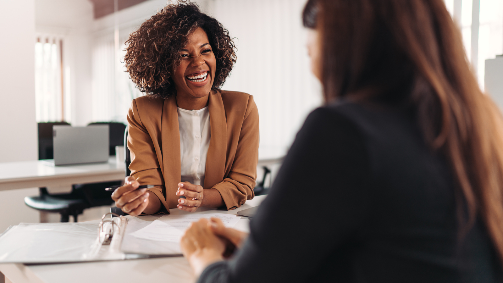 Image showing a client meeting with two women. Maintaining client relationships is essential for businesses - eSign Genie can help.