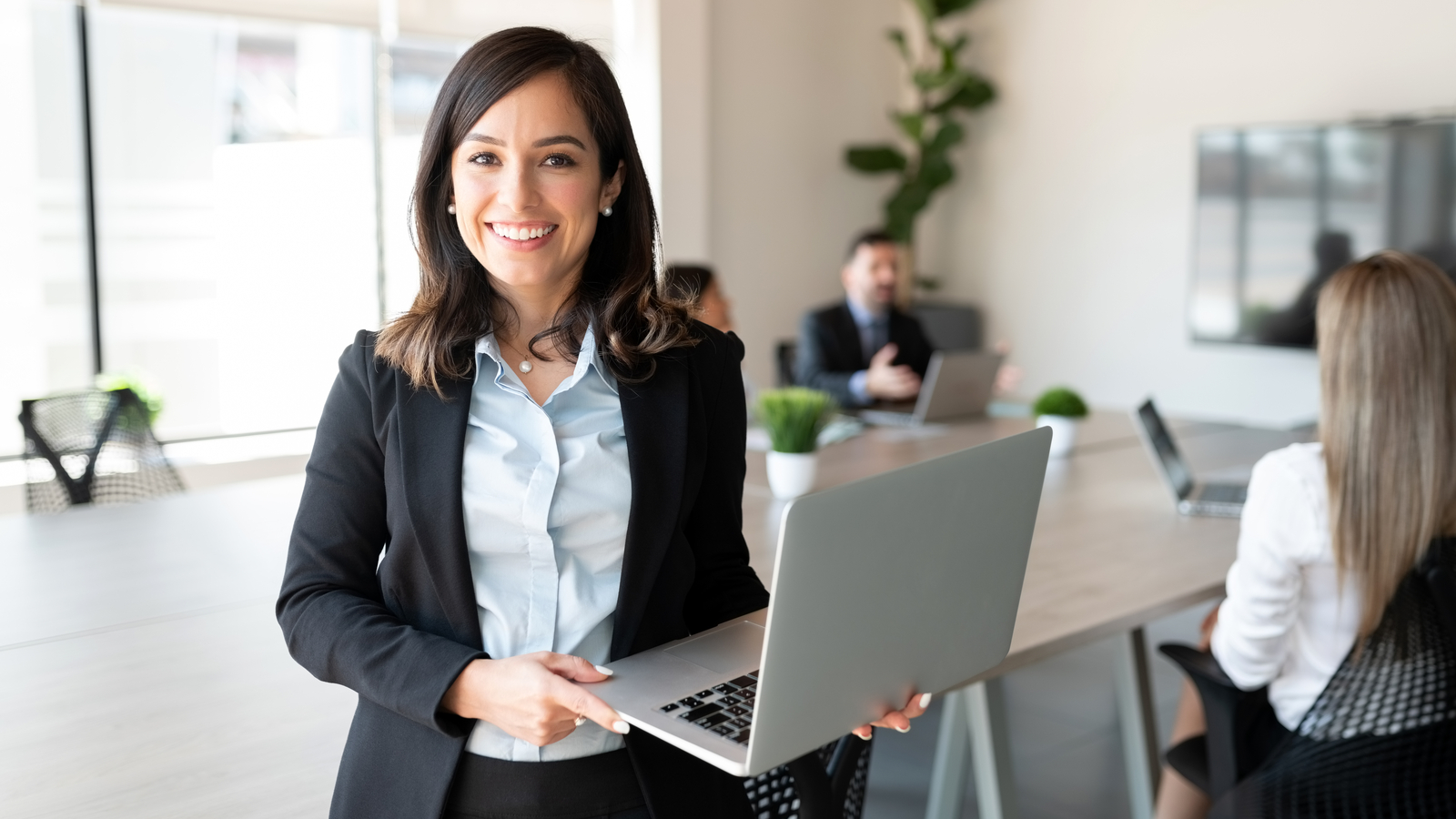 Image of smiling IT manager holding laptop. Electronic signatures are being increasingly used by IT managers and administrators to streamline workflow efforts.